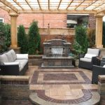 Comfortable Backyard Patio Design Idea With Wooden Beige Pergola And Black Upholstered Rattan Sofa Design And Patterned Paved Flooring And Waterfall And Outdoor Kitchen Set