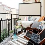 comfortable balcony decoration idea with white board and black fence and carpetted floor and black chairs and coffee table