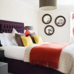 comfortable bedroom design with spring mood and red sheet and purple headboard and round wall mirrors