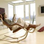 comfortable-brown-Gravity-reading-chair-and-multifunction-as-rocking-chair-and-recliner-with-a-women-read-a-book-near-a-tv-on-the-white-wall-also-soft-beige-floor-and-glass-window