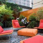 Comfortable Outdoor Living Seating With Red Target Outdoor Cushion Idea And Orange Pouff On Stone Pation And Wooden Fence