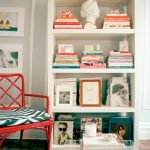 comfortable personal library idea with coral color book cover and chair and green area rug and gray wall paint
