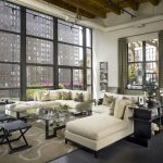 comfortable-soft-beige-sofa-in-industrial-living-room-with-soft-beige-pillows-and-glass-sofa-table-and-carpet-on-the-dark-wooden-floor