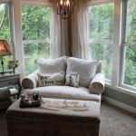 comfortable-white-oversized-chair-with-ottoman-for-reading-and-relax-in-the-corner-with-chandelier-and-table-lamp-and-a-grey-carpet