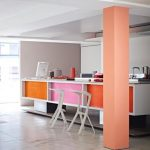 concrete kitchen flooring idea in white interior with orange and pink bar table and white stools and coral colored beam