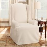 cotton duck slip cover for chair in natural white combined with round wooden end table with drawer and storage plus attractive brown rug and white standing lamp