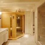 creamy and spacious bathroom idea with walk in shower and white  vanity with wooden sauna with glass door