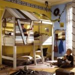 creative-and-enjoyable-tree-bunk-bed-for-kids-with-ladder-and-accessorized-with-snake-toy-and-rope-near-yellow-wall