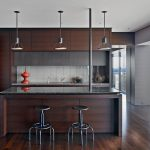elegant and dark home bar idea with open concept and metal stools and vault pendants and wooden floor and wooden cabinetry
