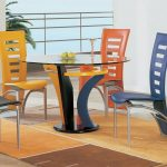 elegant and luxurious colorful unique dining chairs in blue orange and yellow and black and round glass dining table and wooden floor