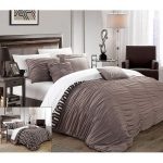 Elegant And Simple Two Side Duvet Cover In Extra Size  Two White Pillows And Four Grey Pillows A Black Corner Armchair A Metal Side Table With A Modern Standing Lamp Black Coated Wooden Bedside Table