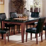 elegant black granite dining table set in rectangular shape with wooden leg and 5 chairs completed with beige rug on wooden floor and classy centerpiece