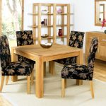 elegant black with floral pattern upholstered chair design with wooden leg and wooden table and white area rug and wooden floor and wooden storage and glass window