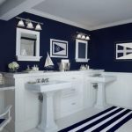 elegant-sea-themed-and-navy-themed-bathroom-with-white-and-dark-blue-color-with-white-flower-and-white-ship-decor-and-two-mirrors-and-navy-flag-pictures