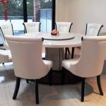 elegant white round granite dining table set surrounded by white classy leather chairs with tufted accent plus sophisticated wood flooring and sliding glass door