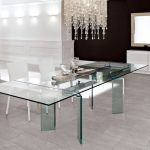 Endearing Super Large All Glass Dining Table Design With Luxurious Chandelier And White Modern Chairs And Black White Wall Paint Design And Concrete Flooring