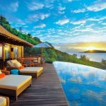 exotic modern resort design with wooden deck and luxurious pool chairs idea and ocean view and sunset