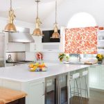 french style modern kitchen studio idea with pink patterned curtain on white cabinet with white large island with white stools and wooden table and copper pendants
