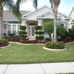 front yard landscape plans with red flowers and trees plus beautiful white house