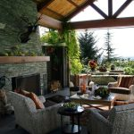 Gorgeous Backyard Patio Design With Mountainous View And Canopy And Stone Fireplace And Gray Sofa And Wooden Table And Cheddar Ornament