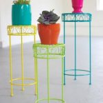 gorgeous colorful indoor plant idea with colorful pots and wrought iron flowe stand in green yellow and blue