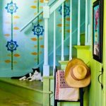 gorgeous hallway idea with blue patterned wallpaper and green wooden staircase with storage
