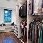 gorgeous white dressing room design with white storage and wooden floor and blue glass window