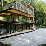 great forest home design with three storey and open plan aside sloping hill with concrete path way