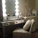 hollywood-style-of-vanity-table-with-lighted-mirror-and-Paris-miniature-and-round-cushion-and-chairs-and-dresser-with-cosmetics