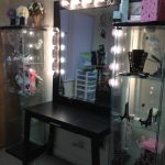 hollywood-vanity-table-with-lights-with-black-table-between-glass-cabinet-and-white-color-wall-and-flowers-and-necklace-and-cosmetics