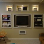 in wall entertainment center built on wall with tv storage and other media storage plus book shelf and comfy chairs plus light rug area