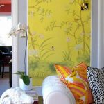 interior design with patterned japanese yellow wallpaper with white sofa and patterned cushions ad wooden end table and orchid