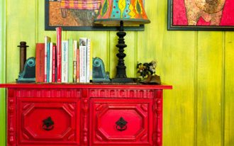 interior with color explosion design with green siding and red console table with frame target wall