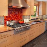 kitchen flooring idea with chevron pattern and creamy cabinet and stone backsplash and orange accent and window