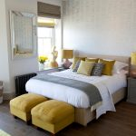 large bedroom decor with white bedding with gray sheet and yellow pouff and wooden floor and yellow table lamp