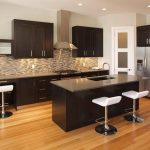 large home kitchen bar design with brown cabinetry and mosaic backsplash and white stools and wooden floor and ceiling lamps