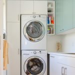 laundry room design with tall cabinet wall cabinet system and under cabinet a washing machine a drying machine