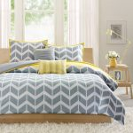 lovely yellow and gray bedroom decor with chevron pattern and open plan and white furry rug and wooden table