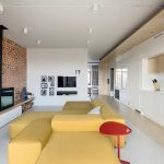 luxurious and spacious living room with kitchen and white cabbinetry and yellow sofa and white console and brick wall