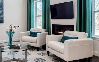 luxurious living room design with white sofa and turquoise cushion and glass window with turquoise velvet fabric curtain idea