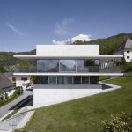 luxurious white modern home on hillside idea with triple floor with glass siding and grassy meadow surrounding