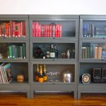 Medium Large Metal Barrister Bookcase For Books Sound Spepaker System And Things And Wooden Floor And White Wall