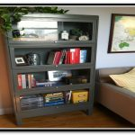 metal-barrister-bookcase-with-four-doors-for-books-photo-clock-and-things-near-beige-sofa-and-pillow