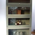 Metal Barrister Bookcase With One Coloumn And 4doors For Books Bottles And Things Near White Wall