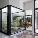 mini indoor greenhouse idea with black framed glass boxes and woodne floor and white ceiling and open plan