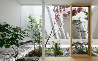 mini indoor greenhouse idea with some types of plants and open plan and wooden framed glass door