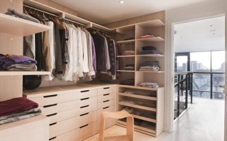modern and posh dressing room design with creamy storage and bench and open concept