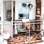modern balcony idea with carpetted floor with gray beach chairs design and floor lamp and storage and wire railing