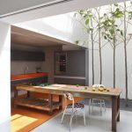modern ergonomic kitchen studio design with indoor plant and skylight and long dining table and modern stools and orange rug and orange cabinet