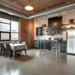 modern industrial loft kitchen design with large glass window and white dining table with black chairs and gray kitchen set